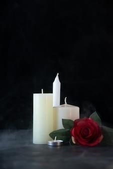 暗い壁に赤いバラの思い出として白いろうそくの正面図