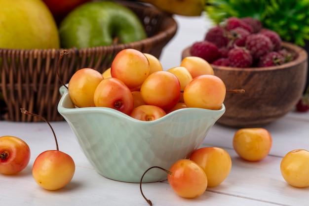 Вид спереди белой вишни в миске с малиной на белой поверхности