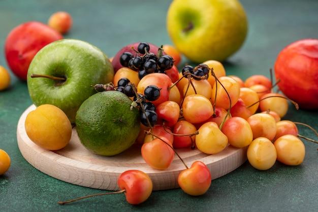 Вид спереди белой вишни с черной смородиной, лаймом, персиком и зеленым яблоком на подставке на зеленой поверхности