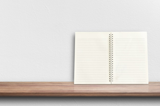 Вид спереди белой тетради на книжных полках для дисплея продукта или модель-макета дизайна.
