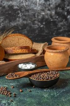 Вид спереди целого и нарезанного свежего черного хлеба на полотенце в коричневой деревянной коробке, гончарные специи на поверхности темных цветов