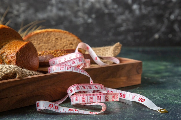 Вид спереди целого и нарезанного свежего черного хлеба на полотенце в коричневом деревянном подносе на поверхности темных цветов