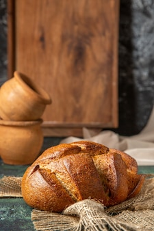 어두운 색상 표면에 갈색 수건 도자기에 전체 검은 빵의 전면보기