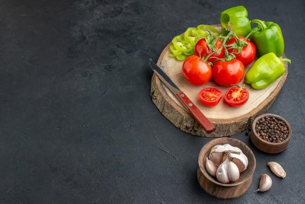 丸ごとカットしたピーマンと新鮮なトマトのナイフ、木製のまな板に唐辛子、ニンニク、黒い面