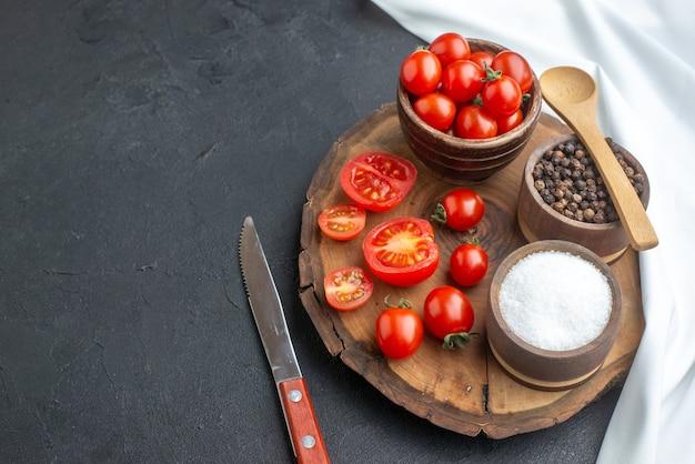 新鮮なトマトとスパイスを木の板に丸ごとカットした正面図、左側に白いタオル ナイフ、空きスペースのある黒い表面