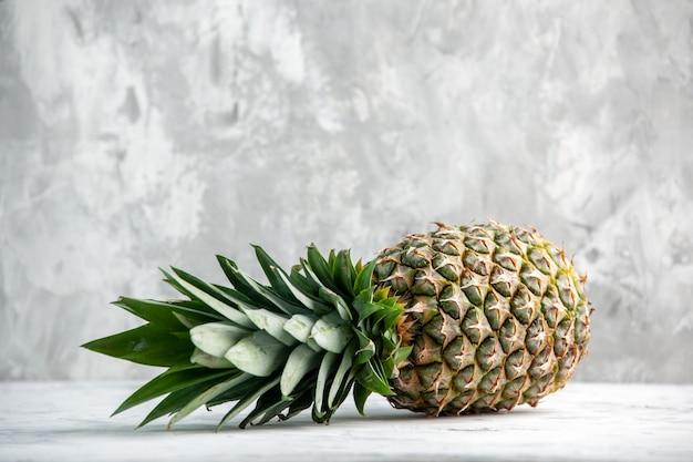 Вид спереди целого свежего падающего золотого ананаса на ледяной стене со свободным пространством