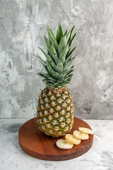 大理石の表面に立っているまな板の上の全体の新鮮な黄金のパイナップルとライムの正面図