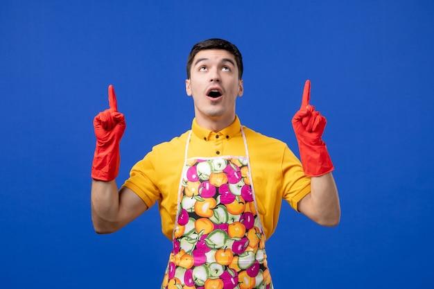 青い壁に立って指で指しているエプロンの目を丸くした男性の家政婦の正面図
