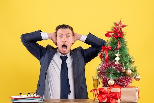 クリスマスツリーの近くのテーブルに座って彼の耳を覆い、黄色で提示する目を丸くした男の正面図