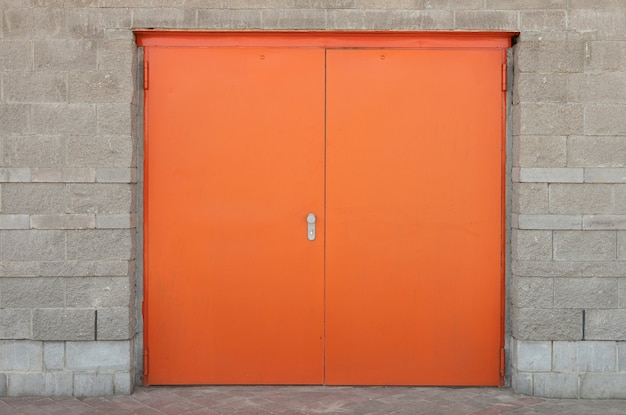 縁取りと灰色の石レンガの壁に設定された広いオレンジまたは明るい赤のドアの正面図