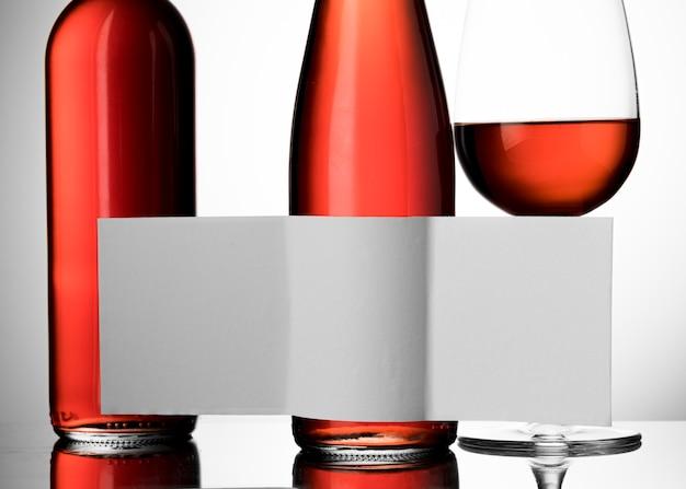 ワイングラスと空白のラベルが付いた2本のボトルの正面図