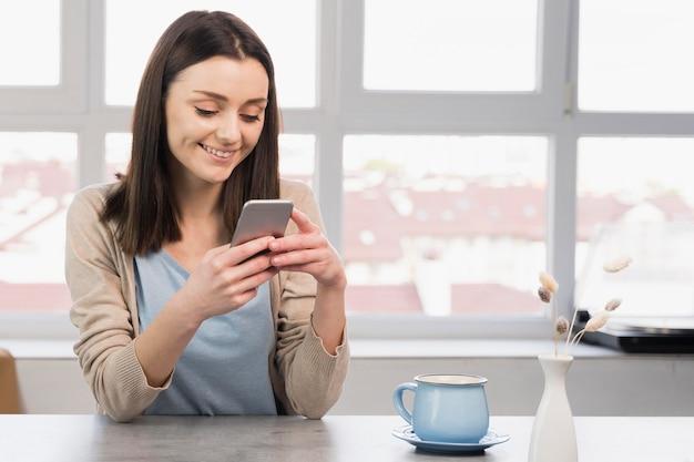Вид спереди женщины на столе, держа смартфон