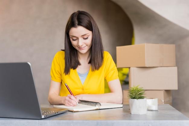 Вид спереди женщины на работе, написание вещи в тетради