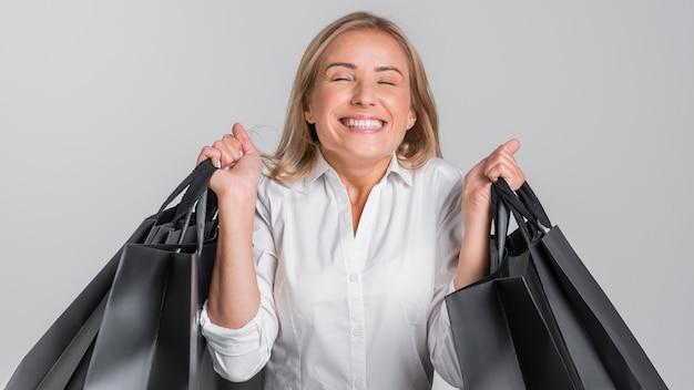 그녀가 계속 한 쇼핑에 대해 행복 해지는 여자의 전면보기