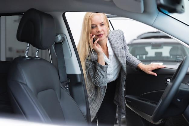 車のインテリアをチェックする女性の正面図