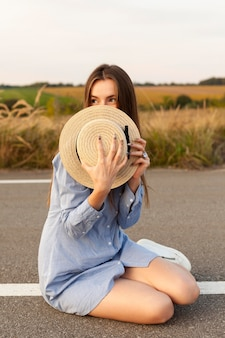 道路の真ん中で帽子で顔を覆っている女性の正面図