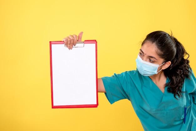 黄色の壁に立っているクリップボードを見ている制服を着た女医の正面図