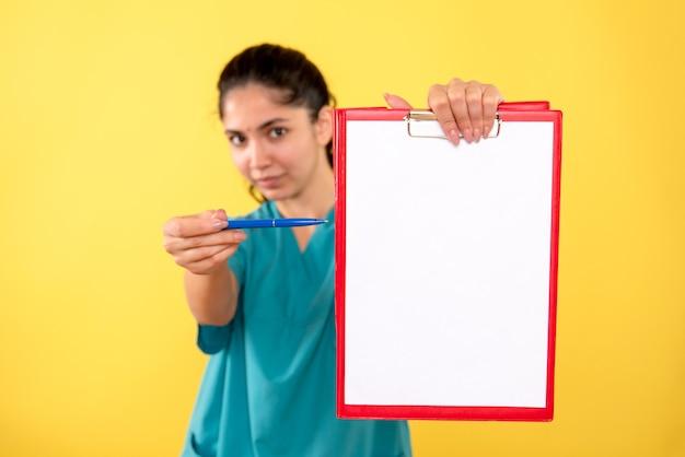 黄色の壁に紙を指して制服を着た女医の正面図