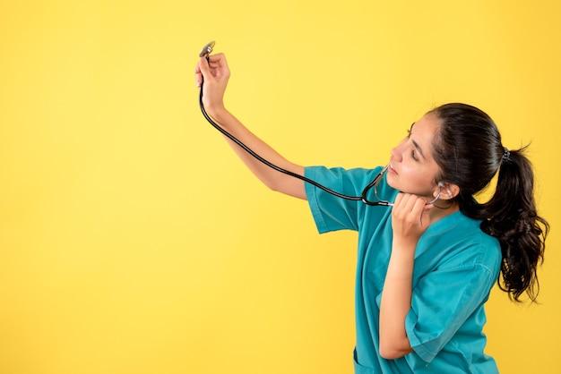 노란색 벽에 청진기를 높이는 제복을 입은 여자 의사의 전면보기