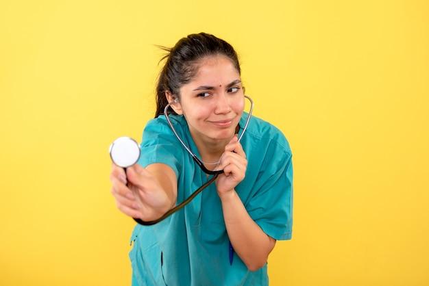 黄色の壁に聴診器を使用して制服を着た女医の正面図