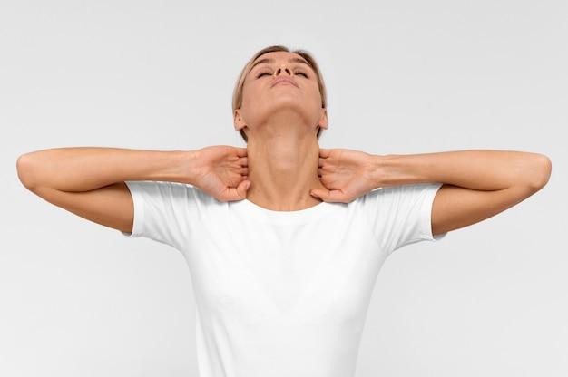 목에 물리 치료 운동을하는 여자의 전면보기