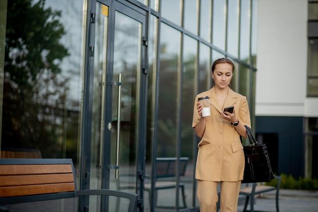 コーヒーを飲み、スマートフォンを持っている女性の正面図