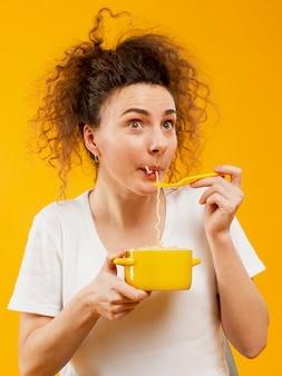 Вид спереди женщины едят лапшу