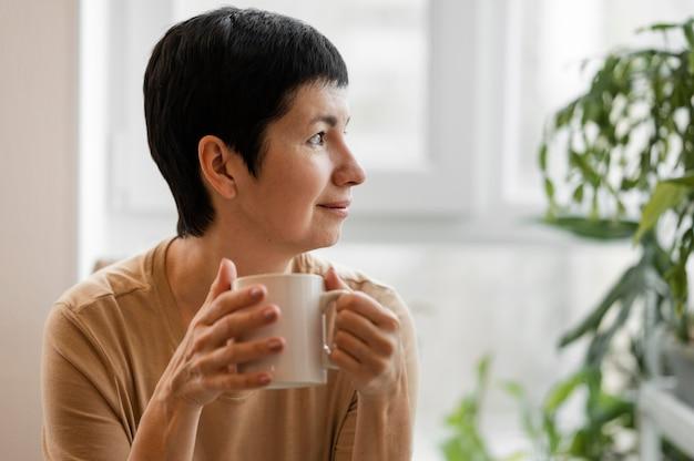 マグカップで飲み物を楽しんでいる女性の正面図