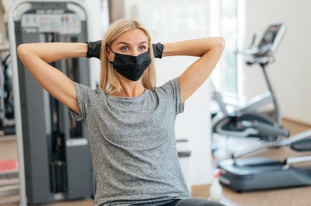 Вид спереди женщины, тренирующейся в тренажерном зале с медицинской маской и перчатками