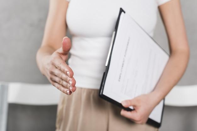 Вид спереди женщины от людских ресурсов, пожимая руку перед интервью