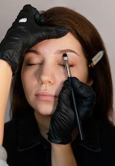 Вид спереди женщины, получающей лечение бровей от специалиста