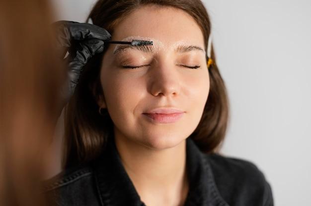 Вид спереди женщины, получающей лечение бровей