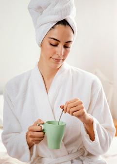 Вид спереди женщины, пьющей кофе дома после ванны