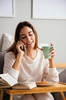 집에서 커피를 마시고 집에서 전화로 이야기하는 여자의 전면보기