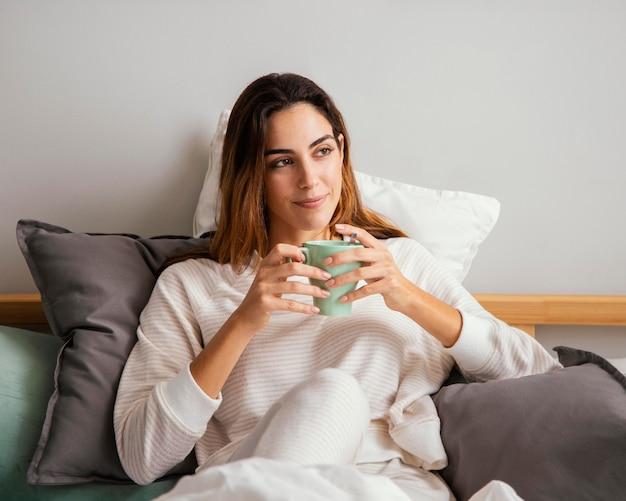 여자가 침대에서 커피를 마시고의 전면보기