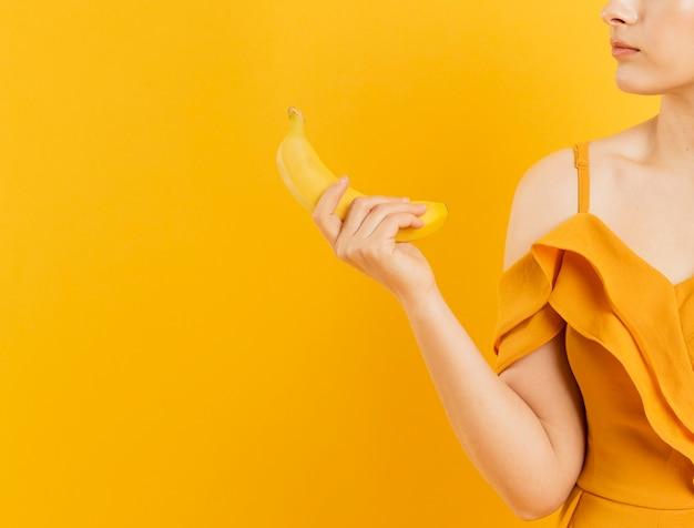Вид спереди женщины, держащей банан с копией пространства