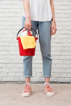 クリーニング用品と布でバケツを保持している女性の正面図