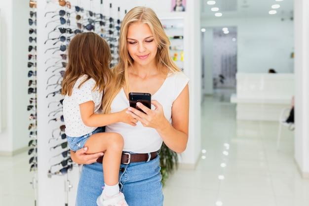 Вид спереди женщины, держащей ребенка и телефон