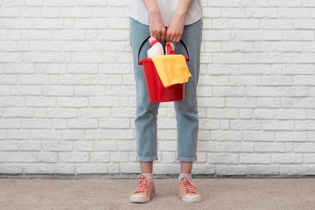 バケツにクリーニング用品を保持している女性の正面図