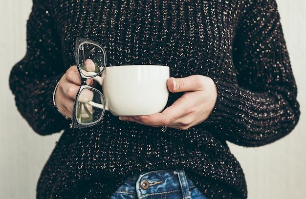 Вид спереди женщины, держащей чашку чая и очки
