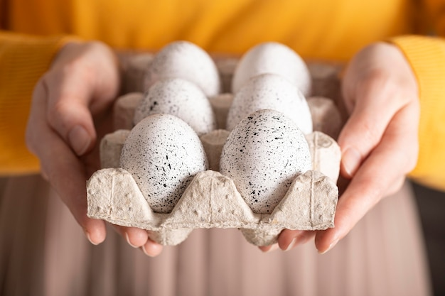 판지에 부활절 달걀을 들고 여자의 전면보기
