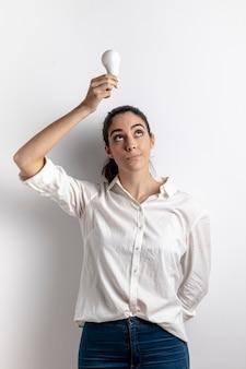Вид спереди женщины, держащей лампочку над головой
