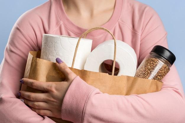 Вид спереди женщины, держащей бумажный пакет с рулонами туалетной бумаги