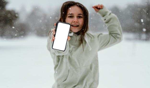 여자가 스마트 폰을 들고 겨울에 야외에서 공중에서 점프의 전면보기