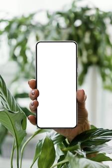 屋内植物の横にスマートフォンを持っている女性の正面図