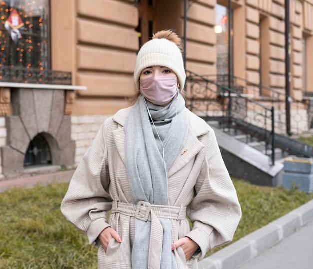 Вид спереди женщины в городе с медицинской маской