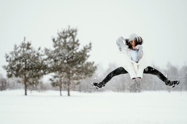 屋外で空中ジャンプする女性の正面図