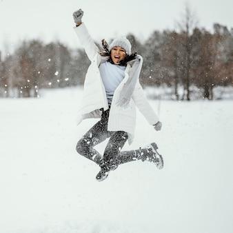 겨울에 야외에서 점프하는 여자의 전면보기