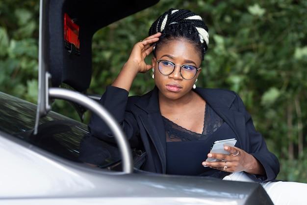 Вид спереди женщины, опирающейся на багажник своей машины, держа в руке смартфон
