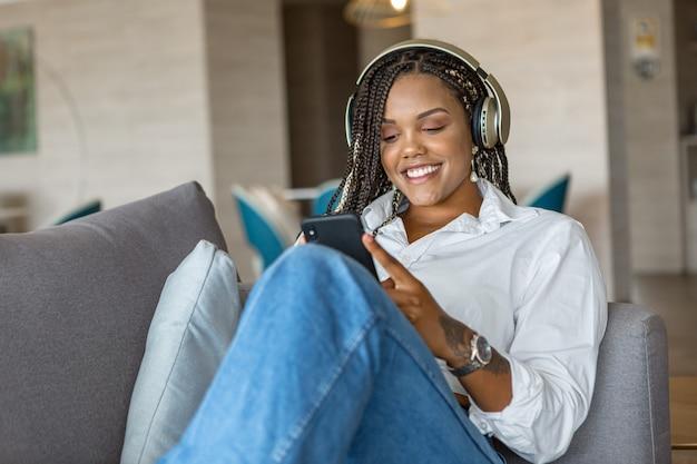 自宅のソファに寄りかかってヘッドフォンで音楽を聴き、携帯電話を使用している女性の正面図。家の人々の概念。